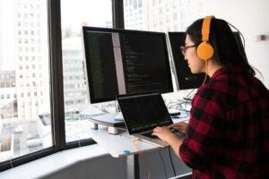 programmeur met meerdere monitors