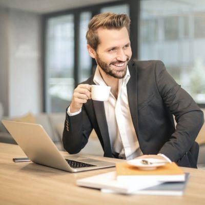 man met laptop en koffie aan het werk